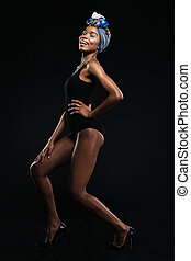 Lovely woman in bodysuit posing isolated on a black...