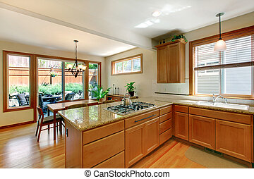 Brown and white kitchen room with hardwood floor, cabinets and eating area.