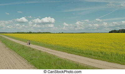The girl and the guy go near the beautiful rape field.