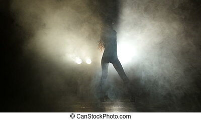 Silhouette of a girl dancing on the background lights. Slow motion