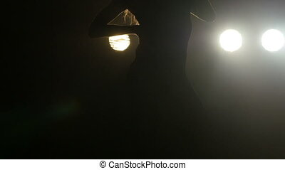 Silhouette of a girl dancing on the background lights. Slow...