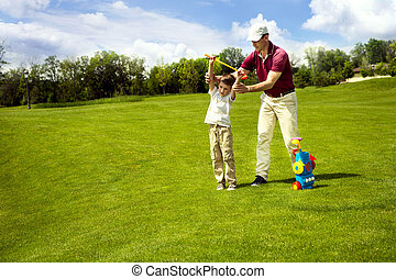 Father with son are training at golf course. Man teaching...