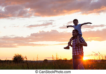 Father and son playing at the park at the sunset time...