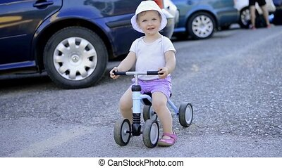 Litle girl riding a bicycle outside in sunny nature - Litle...