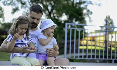Father with his little daughters outside in park - Young...