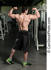 Muscular Man Flexing Muscles Rear Double Biceps Pose -...