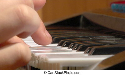 child play at toy piano - close-up playing a simple melody...