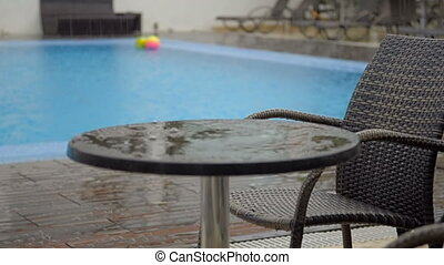Summer rain dripping on the table by the pool in the hotel