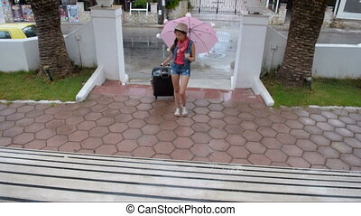 A young girl carries the luggage up the stairs