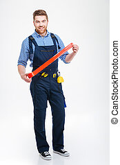 Happy bearded worker standing and using red adhesive tape