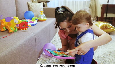 Mom with child playing on children plate tablet