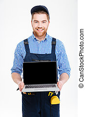 Happy builder in overall and cap holding blank screen laptop