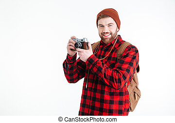 Smiling man holding photo camera isolated on a white...
