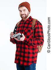 Smiling male hipster holding retro camera isolated on a...