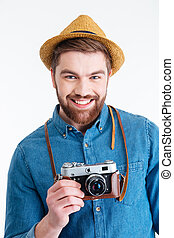 Close-up portrait of a smiling guy holding retro camera -...