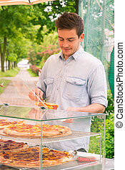 Man selling pizza by slice