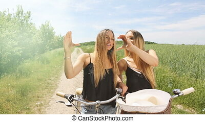 female twins making a heart symbol with her hands. hd. summerfeeling