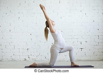 Pregnant young woman doing yoga Virabhadrasana 1 pose -...
