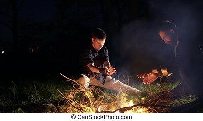 Two men doing moves over bonfire on thr night. 4K.