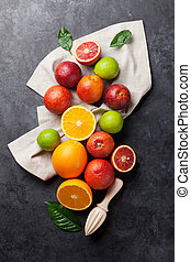 Fresh ripe citruses. Lemons, limes and oranges on dark stone...