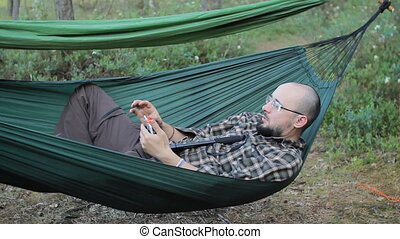 A man in a hammock making selfie on the phone. Man in the...