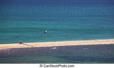 kite surfing on blue sea surface - kite surfing. surfers on...