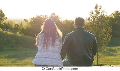 back view of young happy couple sitting at sunset - back...
