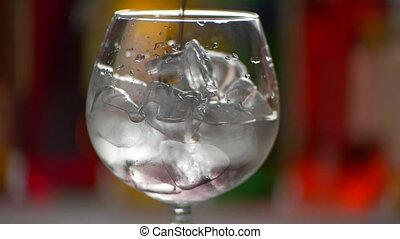 Beverage is slowly pouring. Wineglass with ice cubes. How...