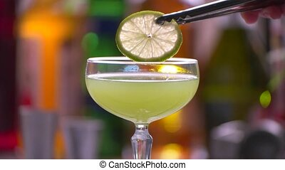 Lime slice slowly falls. Tongs hold slice of lime. Drink...