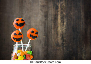 Halloween cake pops and colored candies on a rustic wooden...