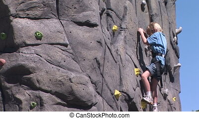 Rock Climbing - Young boy races to the top of the rock...