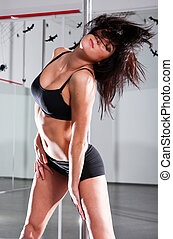Young woman with pole - Young athletic woman dancing around...