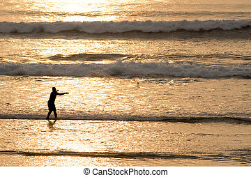 Silhouette of man with fish net on beach water - Fisherman...