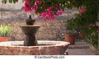 Fountain - Water fountain in a brick courtyard in San Juan...