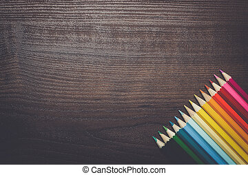 colorful pencils over brown table background - multicolored...