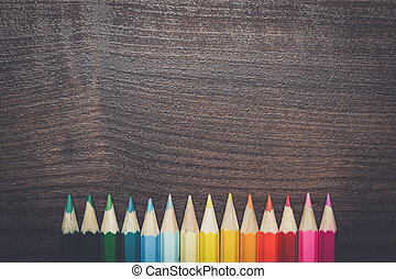 multicolored pencils over brown wooden table - multicolored...