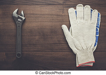adjustable wrench and gloves on the wooden background