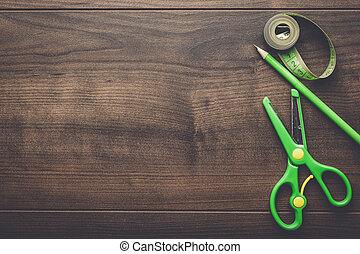 green measuring tape, scissors and pencil on the wooden...
