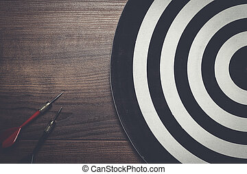 two darts and target on wooden background - target and two...