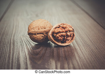 walnuts on the brown wooden table - two walnuts on the brown...