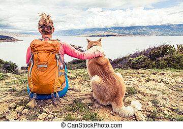 Woman hiker with dog looking at sea - Woman hiker looking at...
