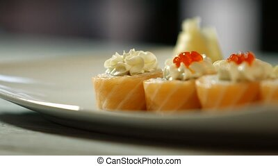 Spoon puts caviar onto sushi. White plate with sushi rolls....