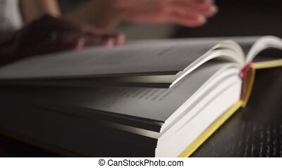 Girl reading and turning over pages of the yellow book clip