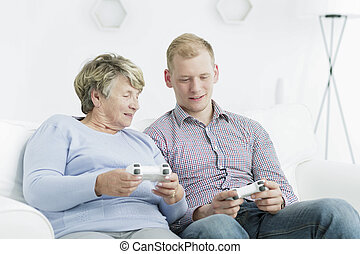 Video games are for everyone - Elderly woman and young man...