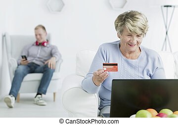 Im paying my bills online - Happy senior woman holdign debit...