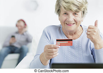 Paying online is cool - Happy senior woman with her thumb...