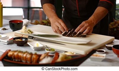 Hands putting sushi onto plate. Man prepares food at table....