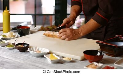 Hands cutting sushi with knife Male cook makes sushi rolls...