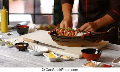 Male hands making sushi boat Man prepares food at table Bits...