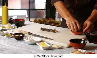 Mans hands making sushi Guy cooks food at table Add some...